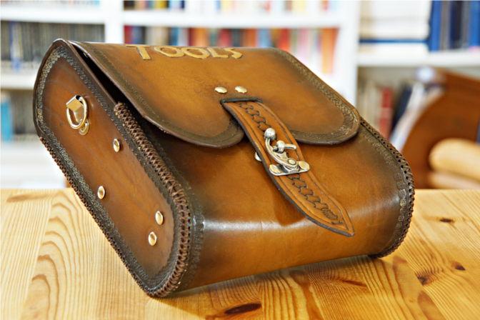 Lederlasche und Verschluss (leider beschädigt) an der Umhängetasche aus Leder. An den Seiten kann ein Trageriemen angebracht werden.(C.B.)
