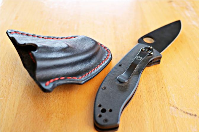 Spyderco Messer neben nassgeformter Lederhülle. Das Messer zeigt den typischen Clip und das Loch in der Klinge.