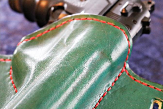 Grünes Holster aus Leder in der Nahaufnahme. Der Kontrast roter Faden/grünes Leder kommt gut zur Geltung.