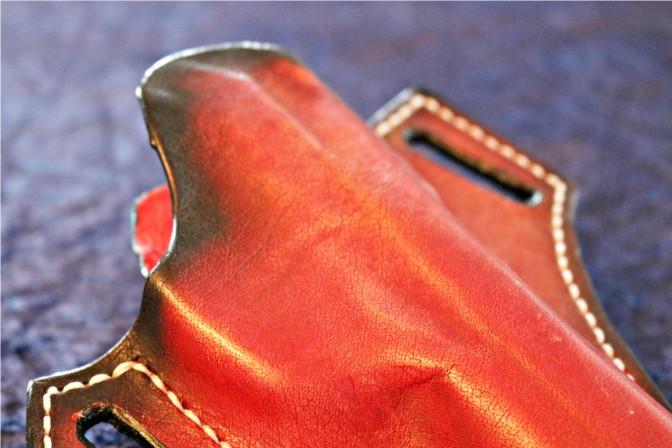 Rotes Holster- oberer Bereich. Die feine Maserung des Leders ist gut erkennbar sowie die schwarze Schattierung.