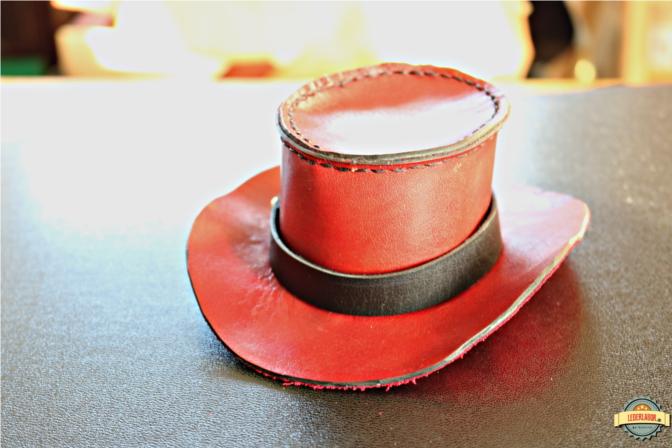 Roter Minizylinder im Detail. Ein schwarzes Band verdeckt die Naht an der Krempe.