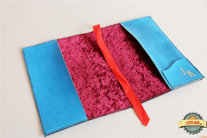 Der Innenbereich des Ledercovers Phex ist mit rotem Pannesamt bezogen und mit einer Tasche versehen, auf der die Initialen des neuen Besitzers zu sehen sind.