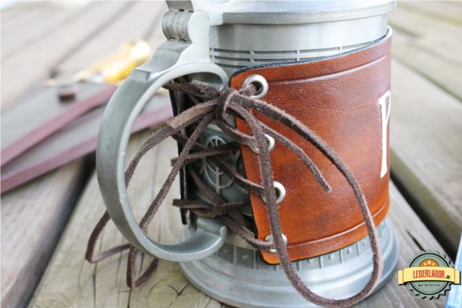 Verschnürtes Lederband um einen Bierkrug.