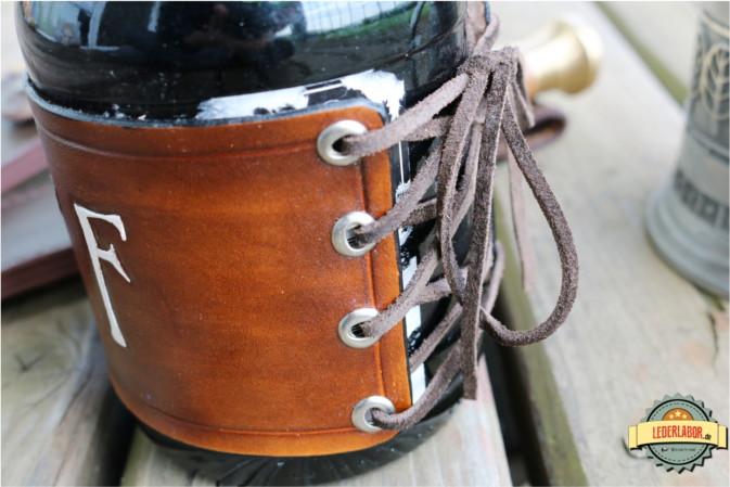 Verschnürung des Lederbandes um eine Flasche Portwein.