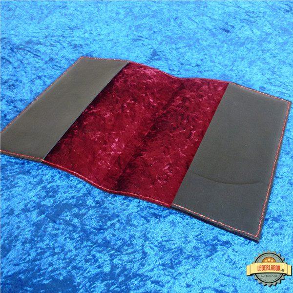 Geöffnetes Ledercover. Die Innenseite ist mit dunkelrotem Pannesamt bezogen. Eine Kartenlasche ziert die rechte Lasche.