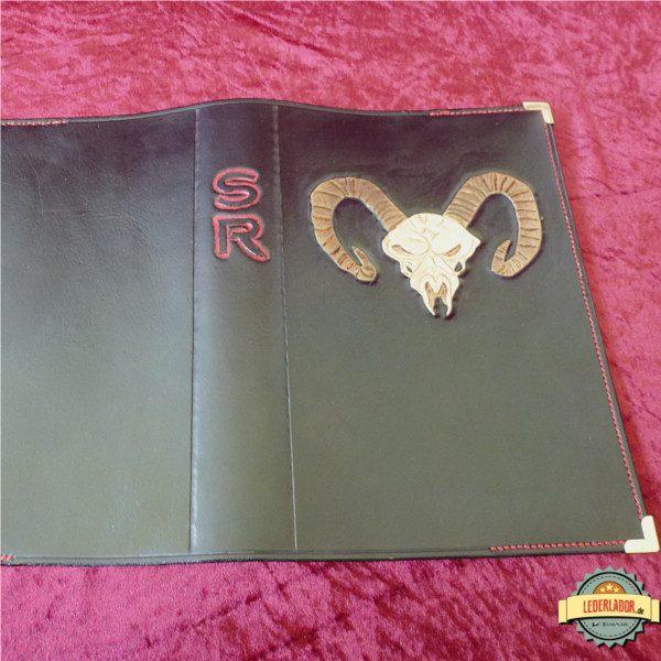 Geöffnetes Ledercover mit Trollschädel und SR Abkürzung.