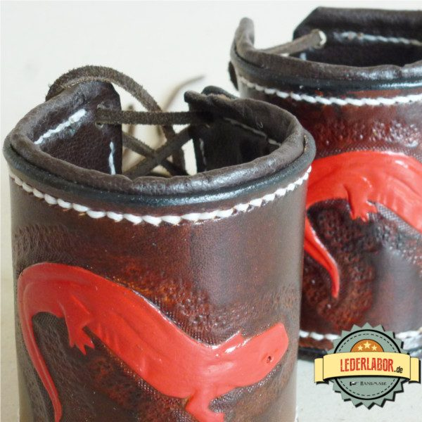 Beide handgefertigte Lederarmbänder mit rotem Salamander Motiv nebeneinander.