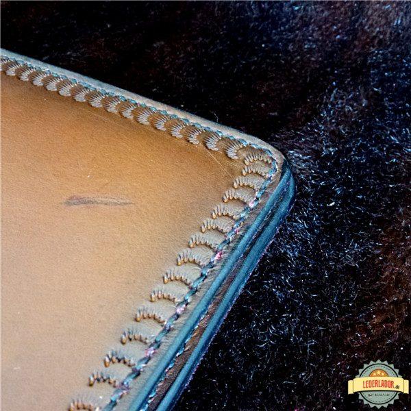 Umlaufende Punzierung und natürliche Narbung des Leders.