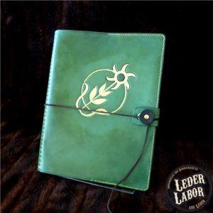 Grüne Ledermappe mit Peraine Symbolik.