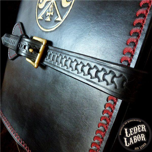 Ledereinband für DIN A4 Ordner mit punziertem Gurtverschluss.